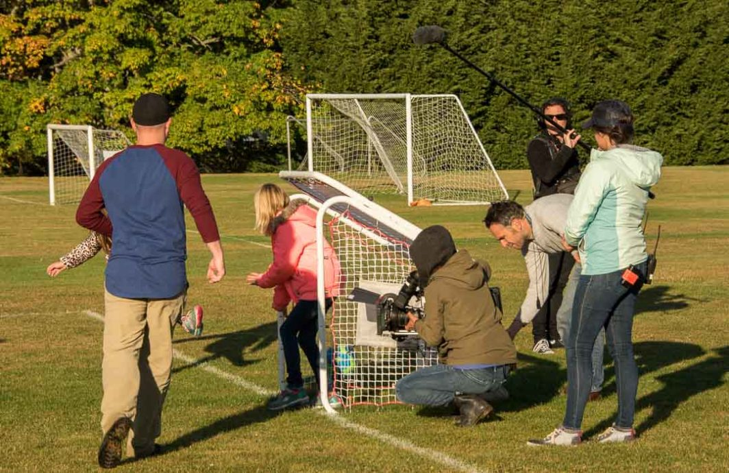 Production company videotaping a family playing soccer.