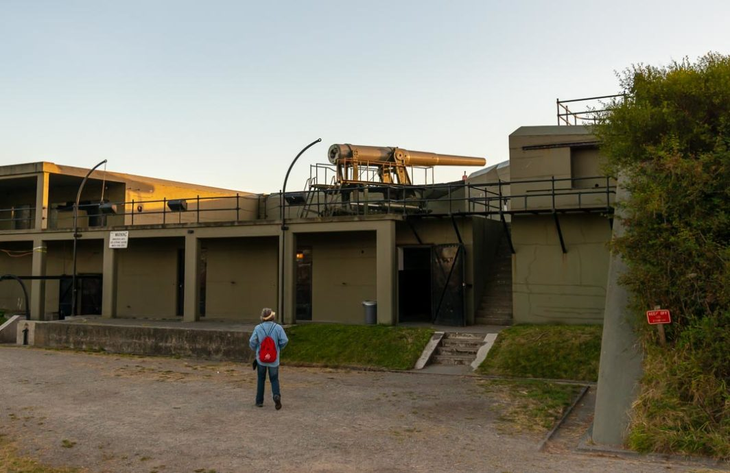 Woman looks at the big gun at Fort Casey.