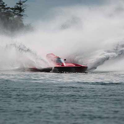 A speeding jet boat sprays water in all directions.