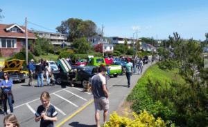 People walk by cars on display.