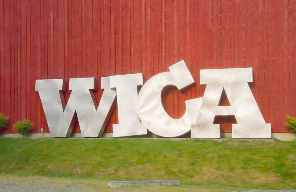 Large metal letters W-I-C_A leaning against a wall.