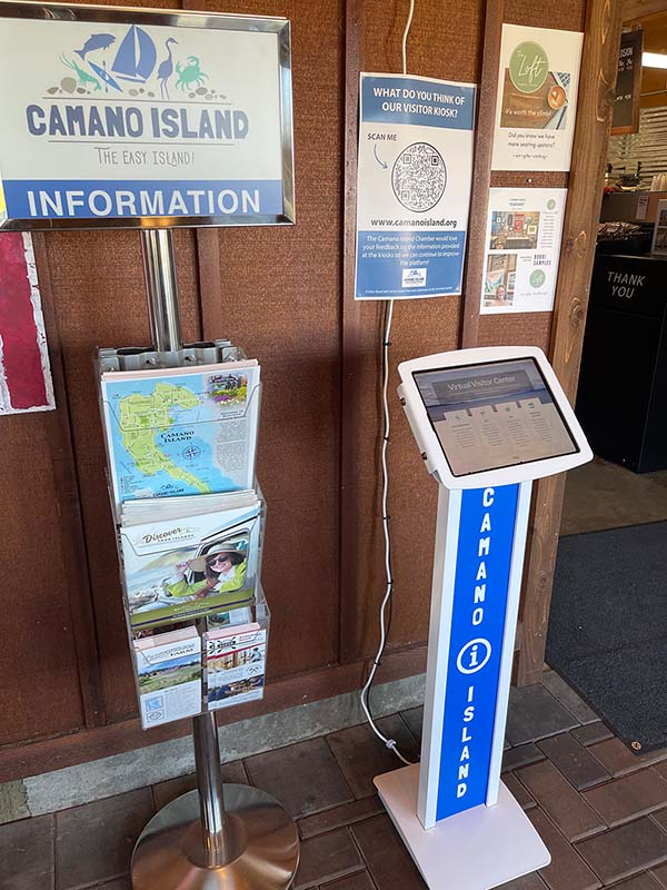 Computer on a stand along with a rack of printed visitor guides and maps