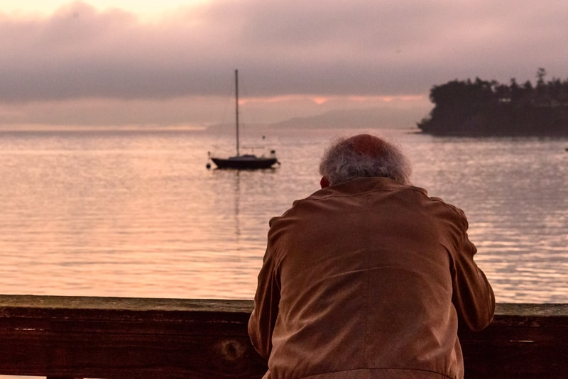 Man standing facing away from camera, using his own camer to photograph a boat.
