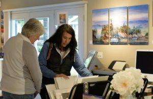 shopers look through paintings on the Camano Island Studio Tour
