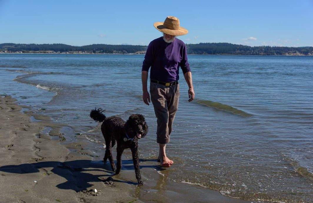 Man walking barefoot with dog on Double Bluff Beach