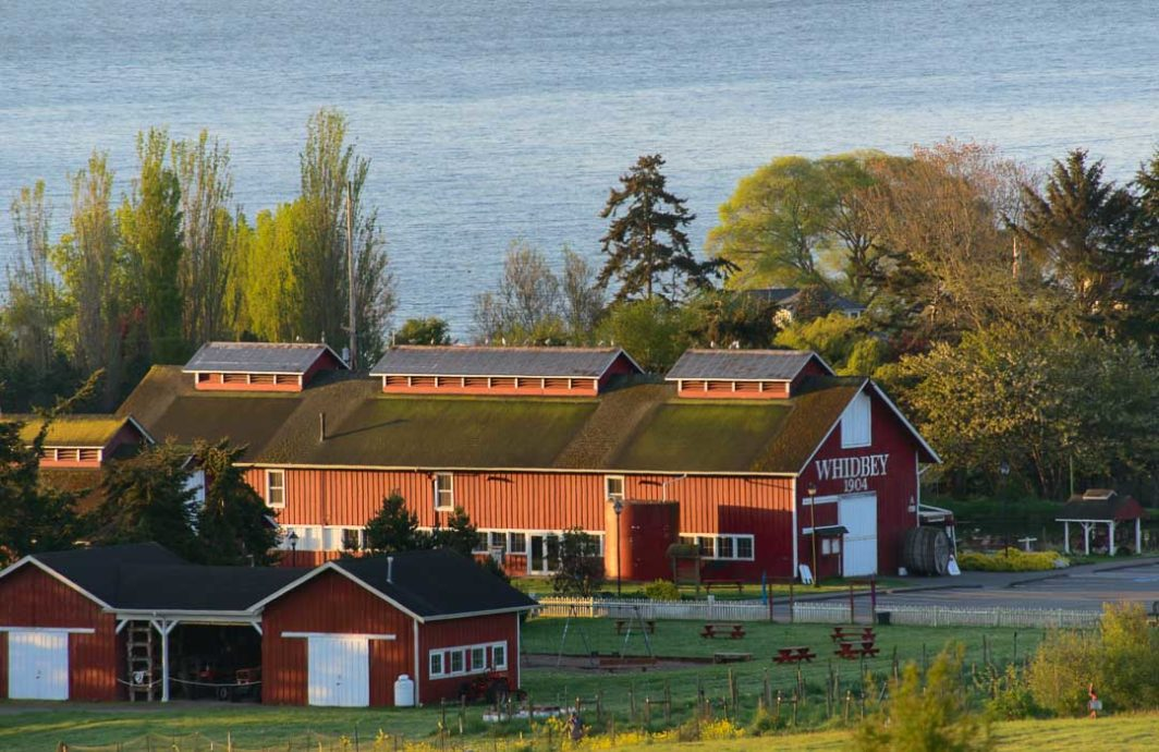 The red barn of Greenbank Farm with the water in the background