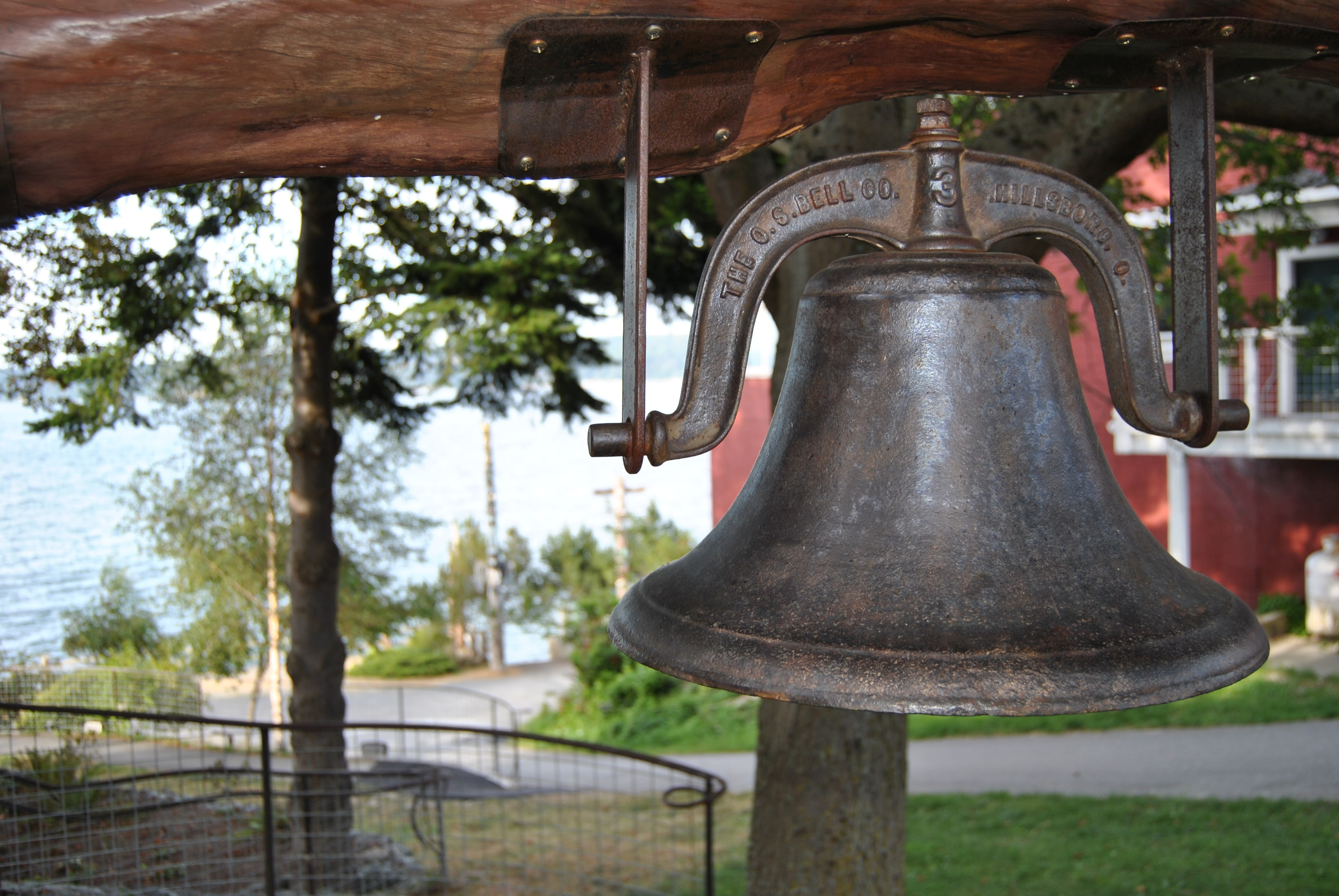 A large bell hangs from a wooden support in a park in Langley.