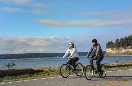 Two people riding bicycles with water and a bluff in the background.