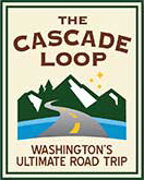 "Cascade Loop Logo shows a highway crossing water and heading into a forested mountain range. The logo says, ""The Cascade Loop, Washington's Ultimate Road Trip."""