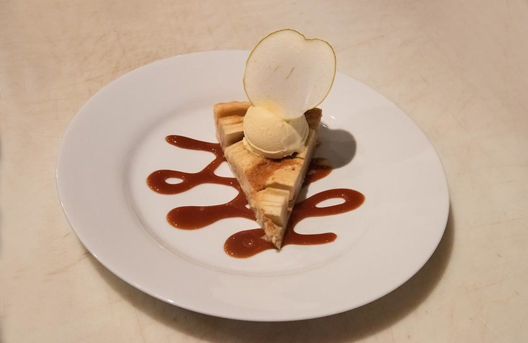 Slice of pie with a scoop of ice cream and a slice of apple in the ice cream