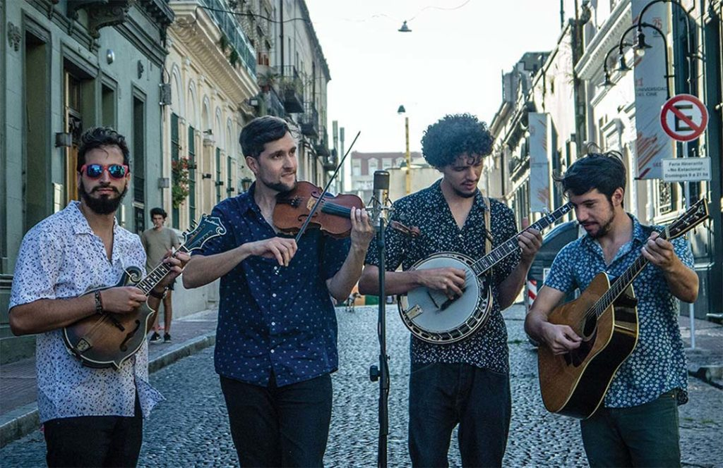 Four musicians playing their instruments in the street