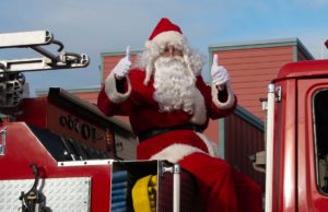 "Santa Claus gives the double ""thumbs-up"" sign while riding a fire truck in the Langley Christmas Parade"
