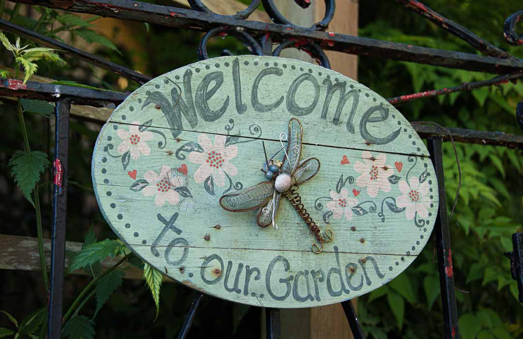 Wooden sign says Welcome to our garden. There is dragonfly made out of metal on it.