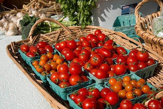 Fresh cherry and grape tomatoes in small baskets for sale