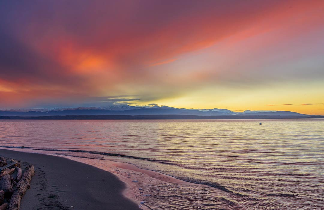 A beach and water with the setting sun and mountains in the distance and colorful clouds overhead.