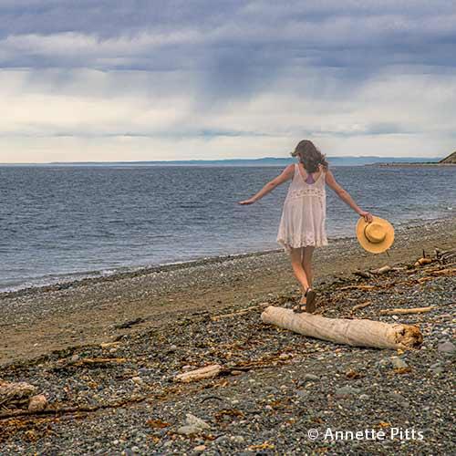 Woman walking atop a driftwood log at Ebey's Landing