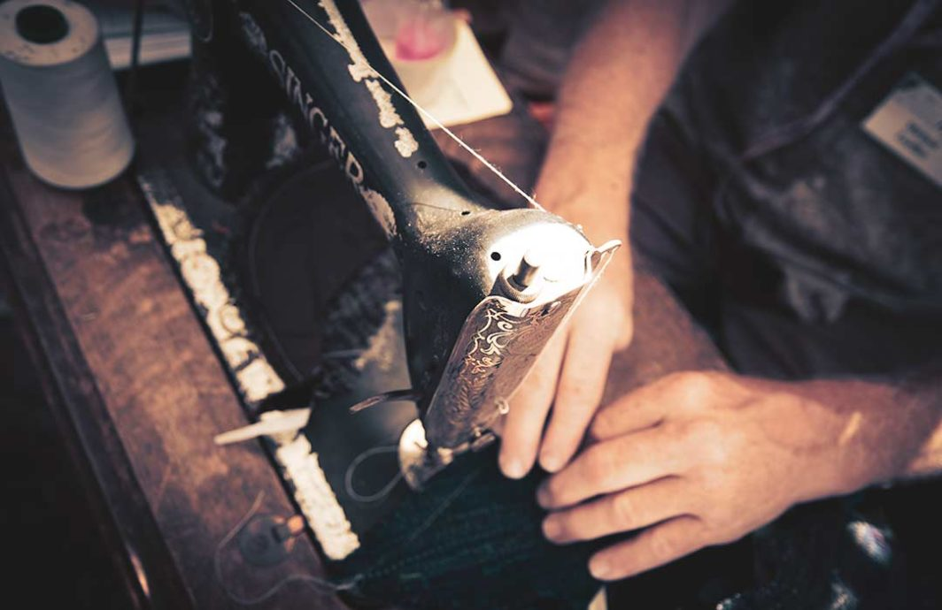 Close up of two hands working at an old sewing machine