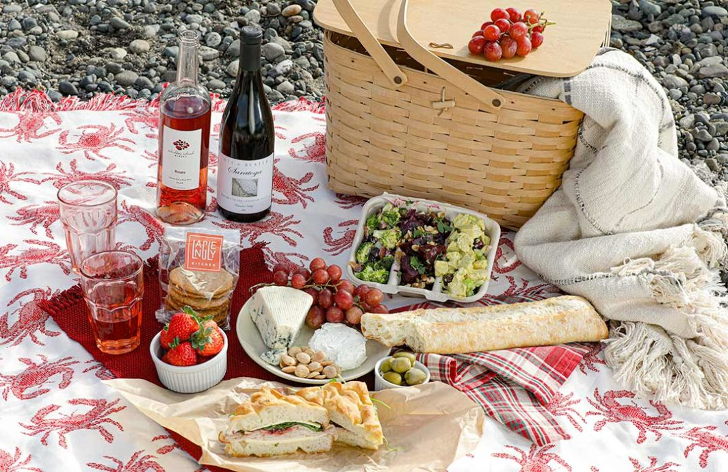 Picnic Basket, bottles of wine, cheese and frut all spread out on a blanket